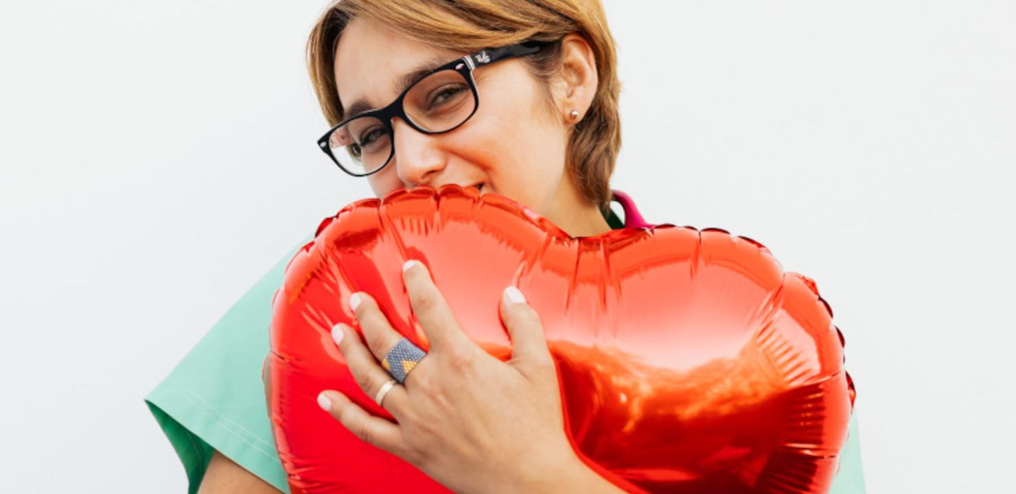 MFA umarmt einen roten metallisch glänzenden Herz-Luftballon